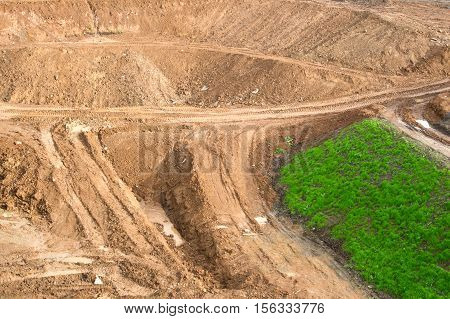 View to the construction of the road type. The high mounds of ground clay stones.