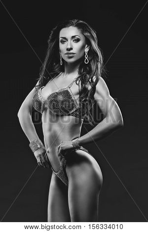 Beautiful muscular young woman with bright makeup in red swimsuit with crystals. Bikini fitness. Studio shot over black background. Copy space. Monochrome.