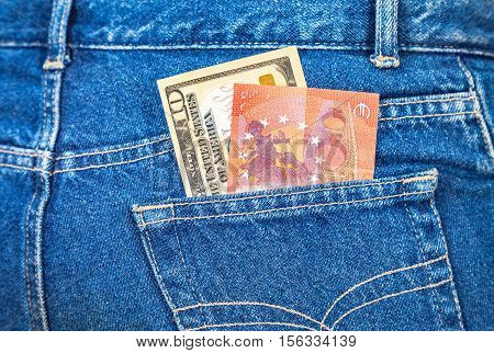 Ten american dollars and ten euro notes sticking out of the blue jeans pocket