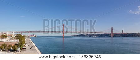 The 25 de Abril bridge spanning over the Tagus River seen from the Belem District. On the right it is seen the famous the Cristo-Rei Sanctuary.