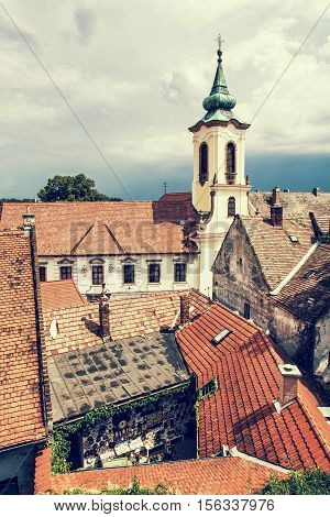 Annunciation church and red roofs of old houses Szentendre Hungary. Religious architecture. Beautiful place. Retro photo filter. Place of worship.
