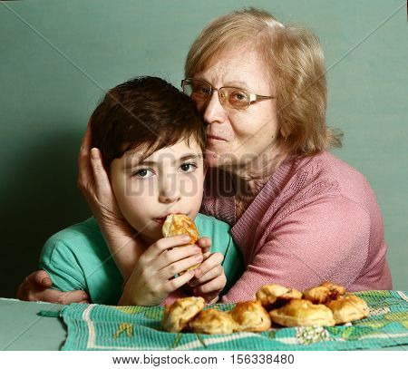 grannie in glasses hug her holding pie grandson close up portrait