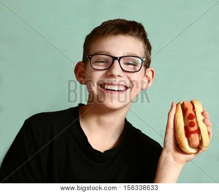 teen handsome boy in myopia glasses with hot dog happy smiling close up portrai