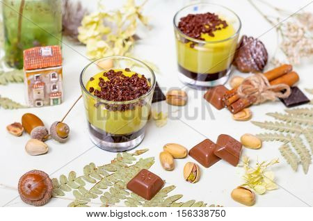 Pistachio dessert served with chocolate, nuts pistachio, fern leaves, dried flowers and cinnamon