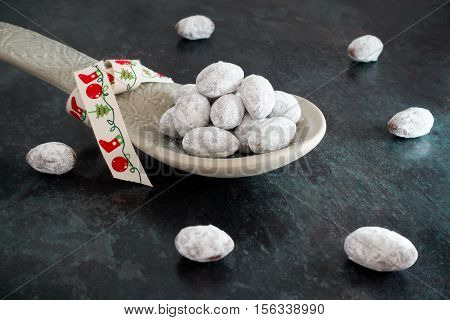 A heap of icing sugar and chocolate coated almonds on an ornamental grey ceramic spoon with Christmas ribbon. Shot on black marbled background. Selective focus and shallow depth of field.