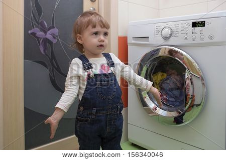 cute little girl doing laundry in home interior. Mother's helper. 2 year old.