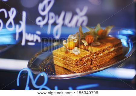Beautifully illuminated showcase pastry shop with delicious honey sponge cake with butter cream decorated with fruits and leaves of physalis on a glass dish close-up.