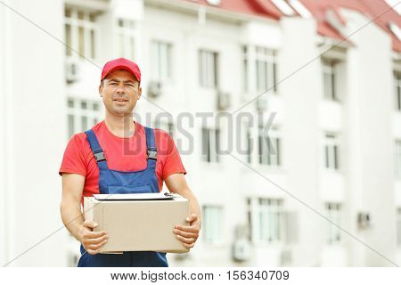 Delivery concept. Postman with parcel on building background