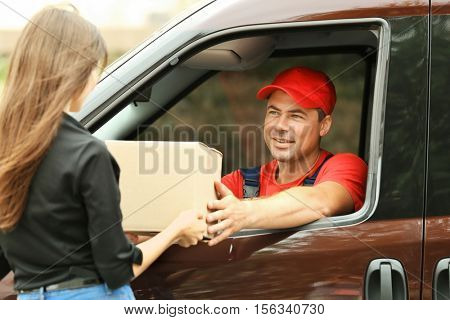 Delivery concept. Postman giving package to woman from a car