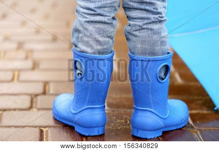 Close up view of boy in blue gumboots standing on wet pavement