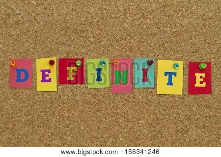 Definite word written on colorful sticky notes pinned on cork board.