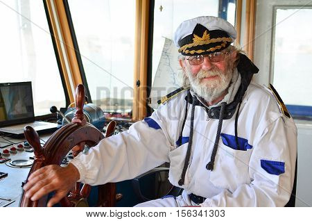 Ship navigation experienced captain old sea dog with grey hair and beard in ship navigation cabine smiling and satisfied after well done job
