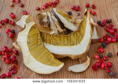 Pile of first class dried bolete mushrooms with red pepper grains on bamboo dark wooden background
