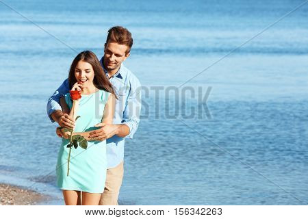 Young man giving rose to his girlfriend on seashore