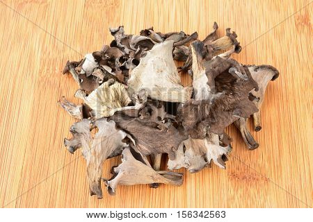 Pile of first class dried Horn of Plenty mushrooms on bamboo dark wooden chopping board