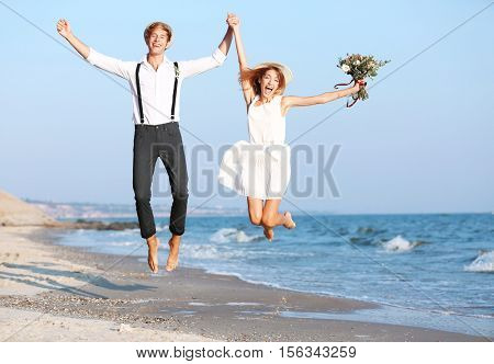 Young happy couple jumping on seashore