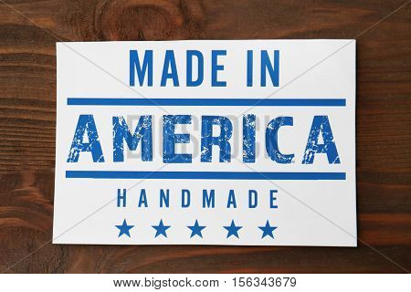 Paper card with text MADE IN AMERICA. HANDMADE on wooden background, close up view