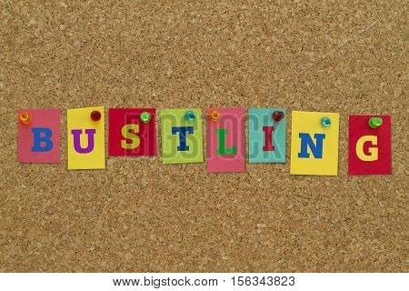 Bustling word written on colorful sticky notes pinned on cork board.