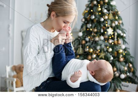 Young mother plays with her little son sitting in a room with green elegant Christmas tree, mother and baby dressed in white knitted sweater and dark blue jeans, a mother and son, blonde hair, a Christmas portrait of mother and baby