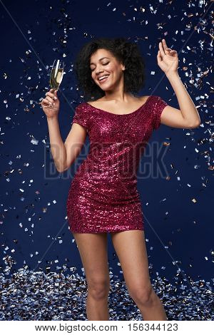 Party, drinks, holidays and celebration concept. Happy young mixed race woman in fancy dress with sequins and confetti at party with glass of sparkling wine