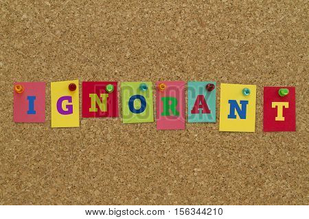 Ignorant word written on colorful sticky notes pinned on cork board.