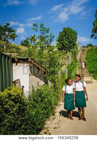 PORT VILA VANUATU OCTOBER 27, 2016: School girls in uniform walk home from classes along a dusty lane in the capital city of the archipelago of 82 volcanic islands in the South Pacific Ocean.