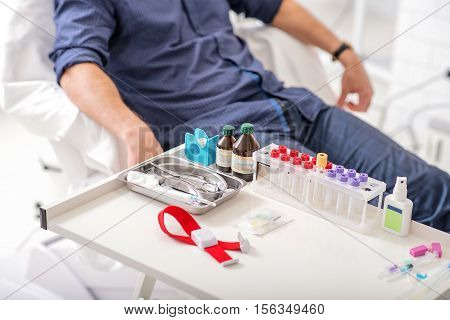 Close up of tools for blood test on tray in hospital. Man is sitting and waiting on background