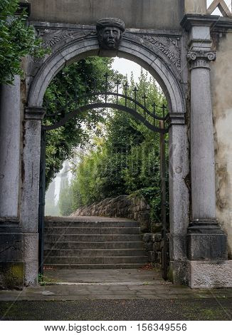 Portoroz, Slovenia - October 17, 2016: The stone arched gateway adorned with decoration and sculptural head. Behind the gate stair and alley in the fog.