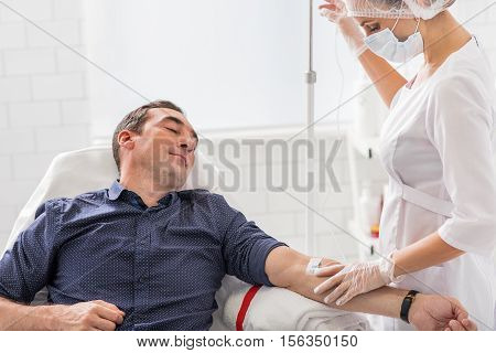 Middle-aged man is having intravenous procedure in hospital. He is sitting and relaxing. Nurse is putting dropper carefully