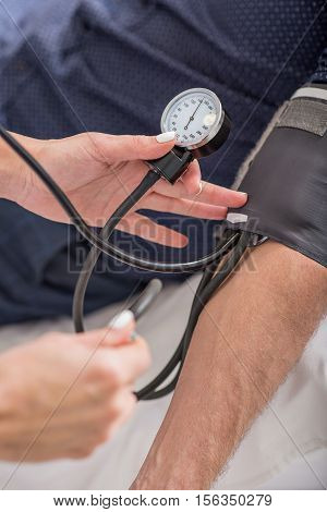 Close up of general practitioner measuring male blood pressure by tonometer