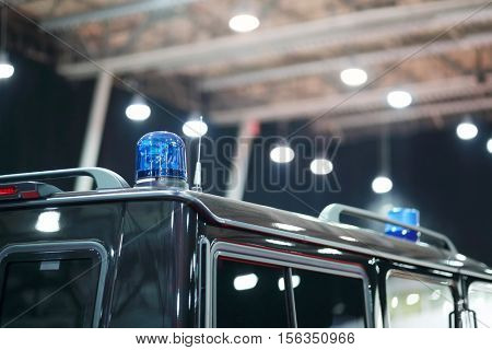 Blue blinker on black car of cortege on auto exhibition, shallow dof