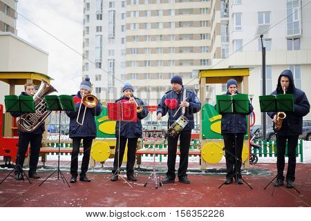 Brass band of six musicians play outdoor at cold winter day on playground
