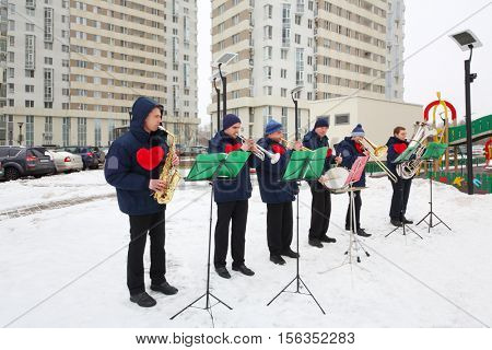 Brass band of six musicians play near building at winter day