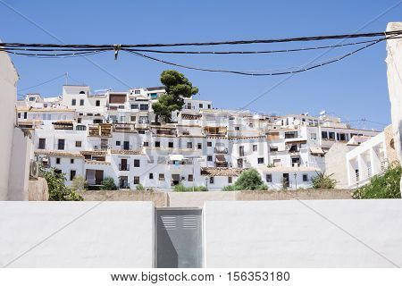 Mediterranean whitewashed tiered homes with sky discected by low powerlines Altea Alicante Spain
