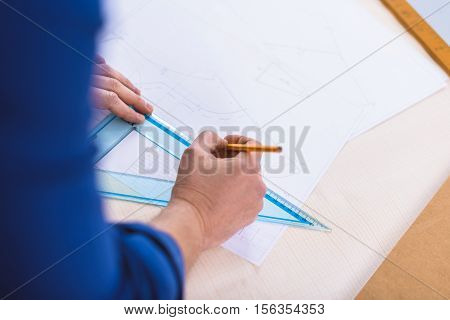 hand of a guy who making an industrial drawing on white paper, top view