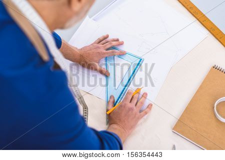 top view of a designer who looking at his drawing of a footwear