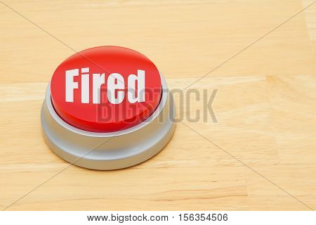 A Fired red push button A red and silver push button on a wooden desk with text Fired