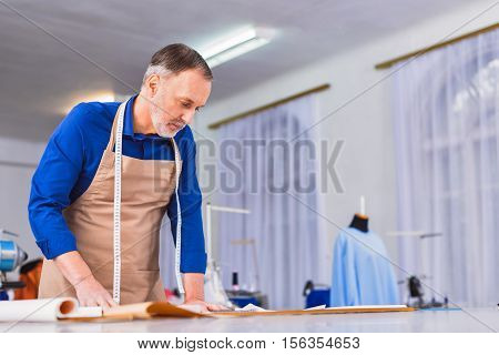 draftsman looking at sketches on a table