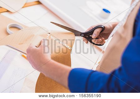 cutting shape of a new shoe on a yellow paper indoors