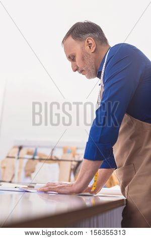 tailor thinking about his new project at the table