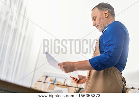low angle view of a modeler with papers in hands with copy space