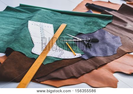 tools of a cobbler on the pieces of leather