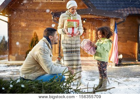 Happy and smiling girl holding Christmas presents which is received from parents