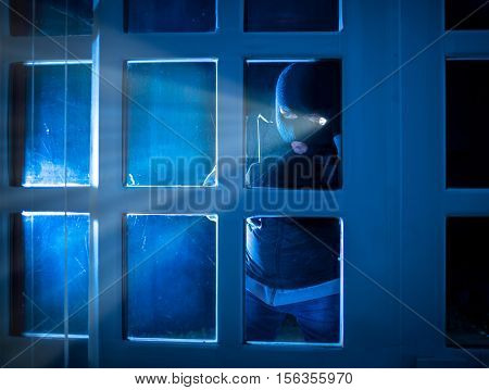 burglar standing in the dark outside and peering inside through glass door