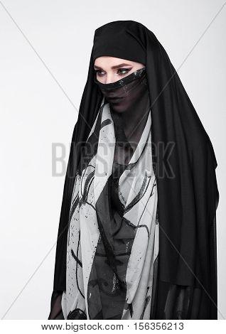 Beautiful eyes woman wearing fashion burka on grey background