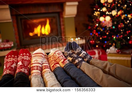 Feet in wool socks near fireplace in winter, family at home near fire