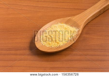 Corn Couscous into a spoon over a wooden table. Cuscus