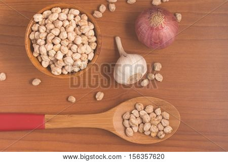 Chick Peas into a bowl over a wooden table