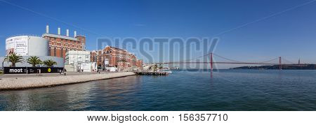 Lisbon, Portugal - October 31, 2016: The Central Tejo, the historical power plant, currently the Electricity Museum and the 25 de Abril bridge spanning over the Tagus River.