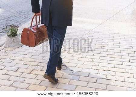 Close up of male legs walking on street with briefcase. Focus on his back